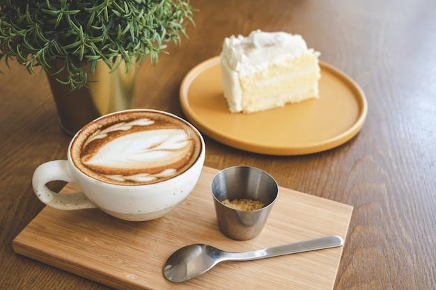 Un'arte del latte della tazza di caffè in caffè della caffetteria sul bordo di legno con un pezzo di dolce