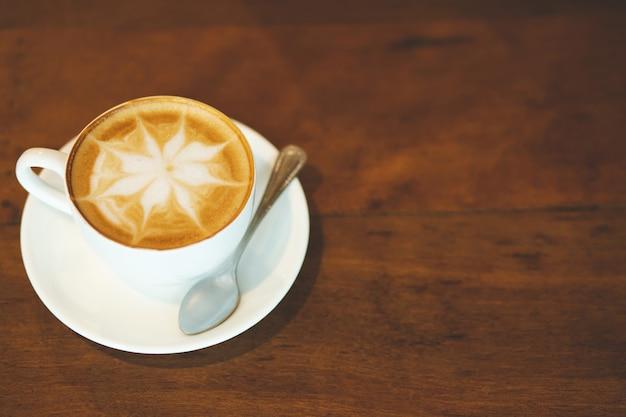 Tazza di caffè latte con forma di cuore e chicchi di caffè su fondo in legno vecchio