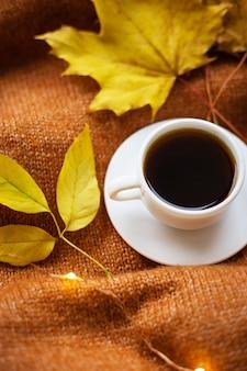 Tazza di caffè e foglie sul maglione