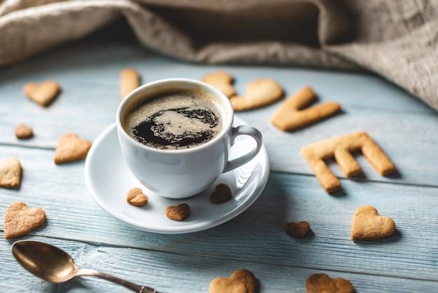 Tazza di caffè e un messaggio da un biscotto dolce sotto forma della parola amore su uno sfondo di legno blu