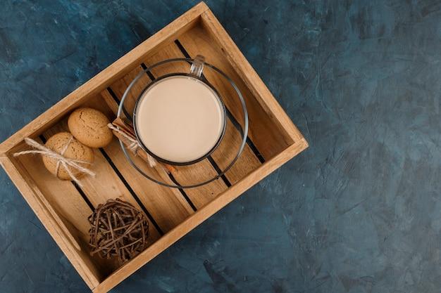 Una tazza di caffè, latte e cannella sul tavolo di legno sullo sfondo blu scuro