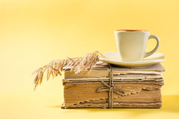 Una tazza di caffè su vecchi libri e spighe di grano secche in giallo. benessere, armonia, lettura tranquilla. copia spazio