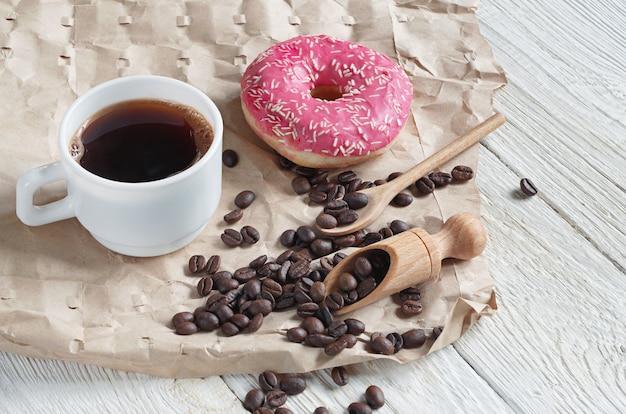 Tazza di caffè e ciambella rosa con spruzza su carta stropicciata