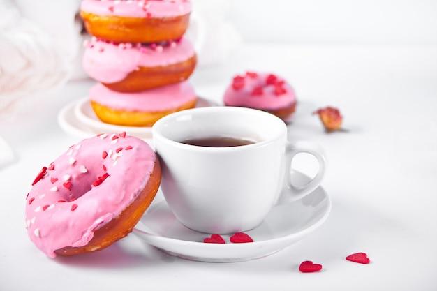 Tazza di caffè e ciambelle rosa su fondo bianco. concetto di san valentino.