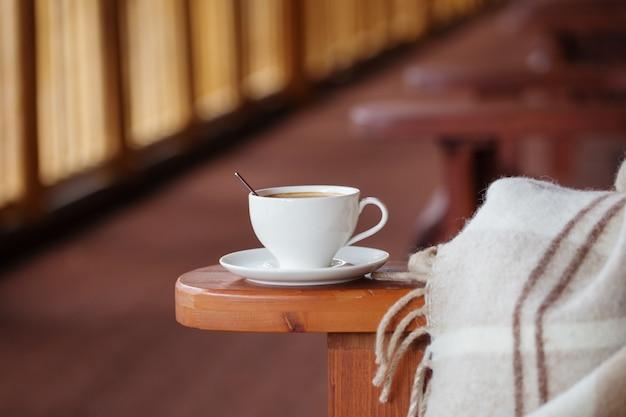 Tazza di caffè e plaid sulla terrazza