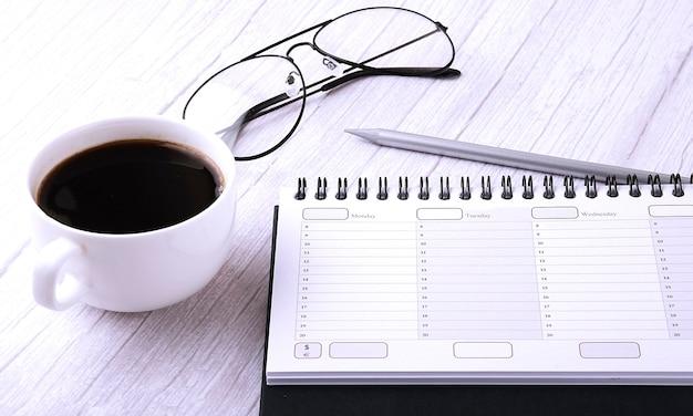 Una tazza di caffè e pianificazione sullo sfondo di legno