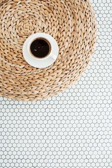 Tazza di caffè su sbuffo di paglia di rattan su piastrelle di mosaico bianco