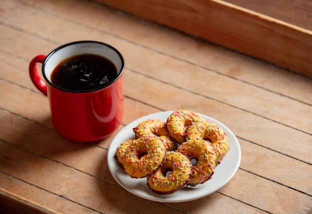 Tazza di caffè in tazza rossa e biscotti sulla tavola di legno
