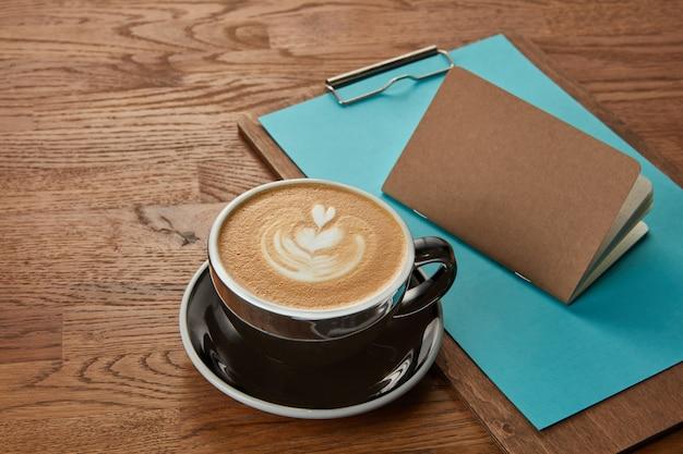 Tazza di caffè rappresentata sulla tavola di legno con taccuino e appunti vicino. delizioso cappuccino, caffè con latte.