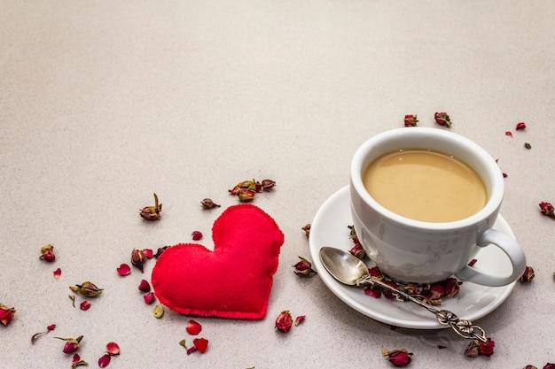 Tazza di caffè, boccioli di rosa e petali e cuore di feltro rosso