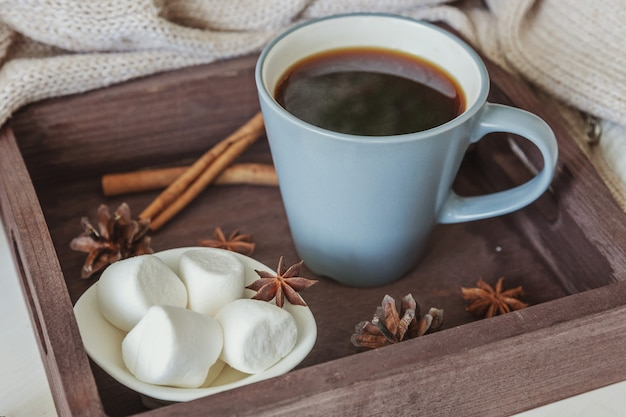 Tazza di caffè sul vassoio in legno rustico con marshmallow dolce e caldo maglione di lana
