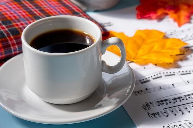 Tazza di caffè su un piattino su sfondo blu. note musicali e una tazza di caffè