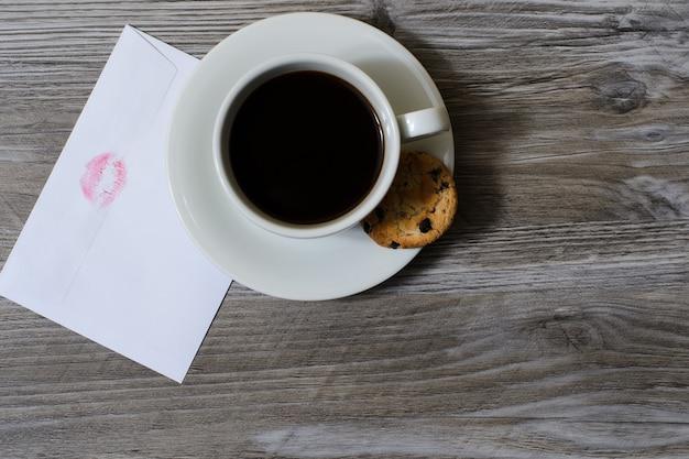 Tazza di caffè sul piattino con busta bianca biscotto al cioccolato con stampa labbra