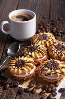 Tazza di caffè e biscotti di pasta frolla con crema e cioccolato sul tavolo di legno scuro