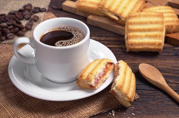 Tazza di caffè e biscotti di pasta frolla con marmellata sul tavolo di legno scuro