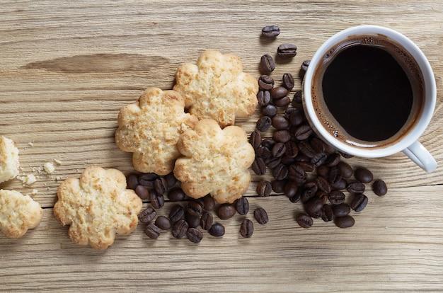 Tazza di caffè e pasta frolla con scaglie di cocco su legno vecchio, vista dall'alto