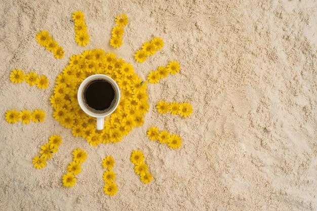 Tazza di caffè, fiore della margherita di singapore sulla spiaggia di sabbia gialla.