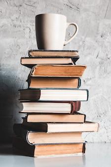 Una tazza di caffè su una pila di libri su sfondo grigio. educazione, studio, hobby, lettura