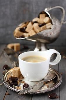 Tazza di caffè, cubetti di zucchero e caramelle al cioccolato su fondo in legno vecchio
