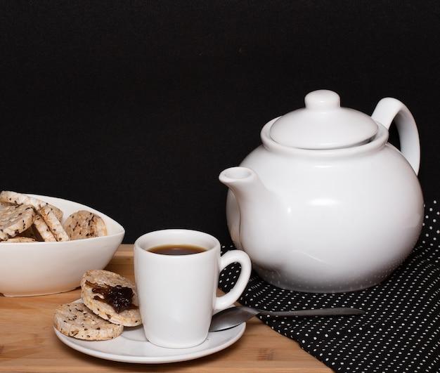 Una tazza di caffè circondava una ciotola piena di biscotti vegani di riso e una caffettiera
