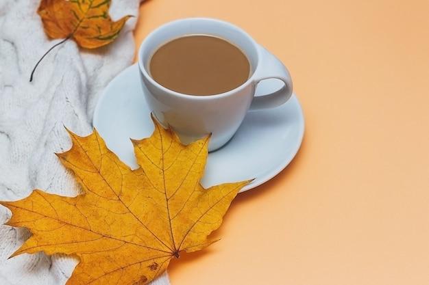 Una tazza di caffè e un maglione su uno sfondo autunnale.