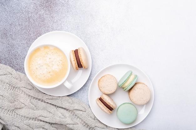 Tazza di caffè, maglione e macarons su fondo di pietra. copia spazio. disposizione piatta, vista dall'alto - immagine