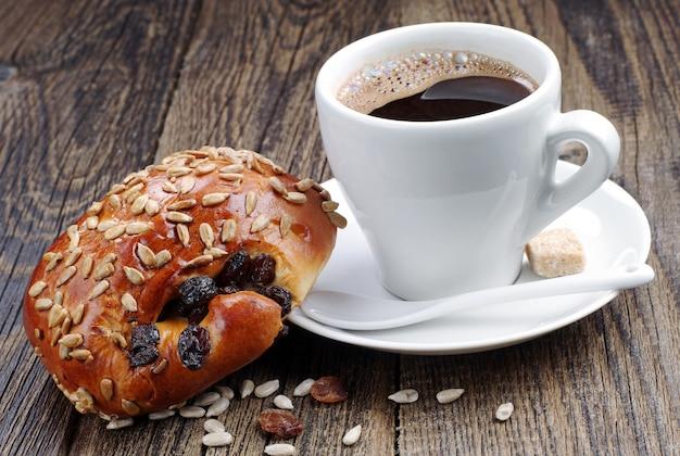 Tazza di caffè e panini dolci con semi di girasole e uvetta sul tavolo di legno