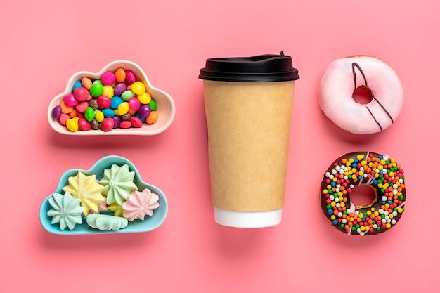 Tazza di caffè, dolci e meringhe in ciotola a forma di nuvola, cioccolato con topping colorato e