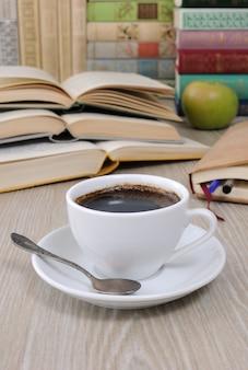Tazza di caffè sul tavolo sullo sfondo di un libro aperto con un quaderno e una pila di libri