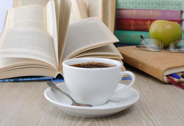 Una tazza di caffè sul tavolo sullo sfondo di un libro aperto con un quaderno e una pila di libri