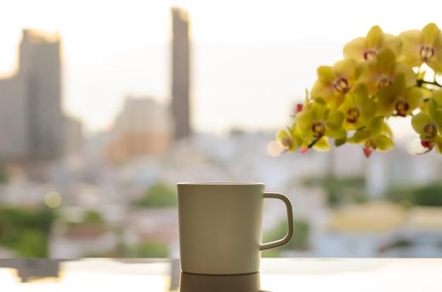 Una tazza di caffè sul tavolo con l'orchidea phalaenopsis e lo sfondo della città al mattino