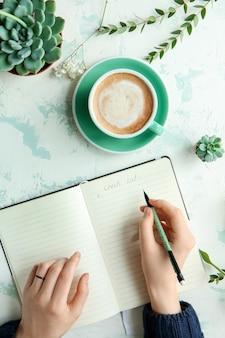 Tazza di caffè sul tavolo della donna che scrive in taccuino