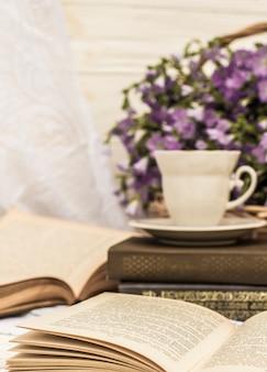 Tazza di caffè (tè), libri e bouquet di lino nel cestino di vimini. stile retrò, vintage