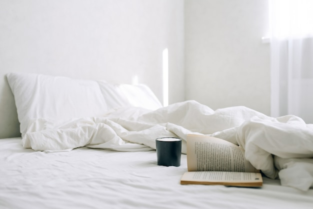 Una tazza di caffè o tè e un libro aperto sul letto nella luminosa camera da letto del mattino