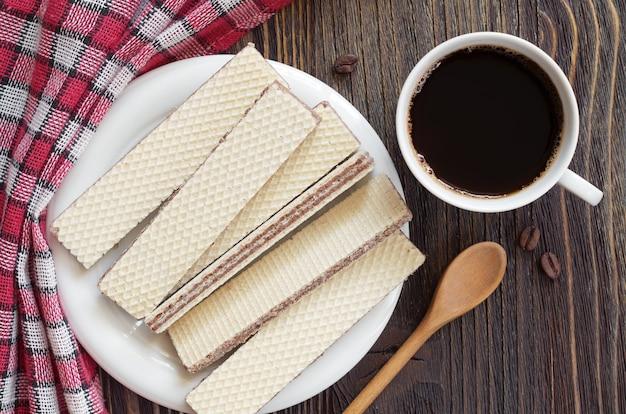 Tazza di caffè e wafer con cioccolato nel piatto sul tavolo, vista dall'alto