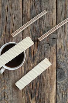 Tazza di caffè e cialde su uno sfondo di legno vista dall'alto