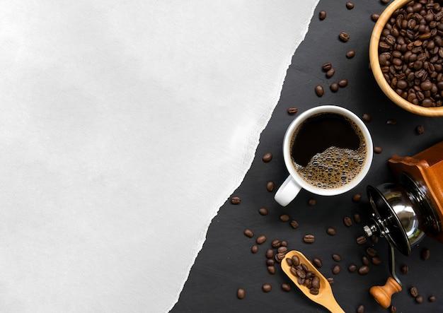 Tazza di caffè, carta bianca e fagioli sul fondo della tavola in legno nero. vista dall'alto