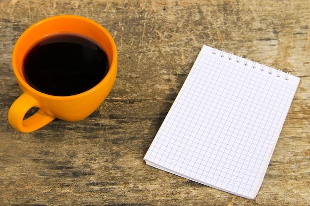 Tazza di caffè con blocco note vuoto su tavola in legno rustico