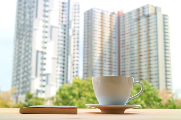 Tazza di caffè con un libro sullo sfondo di edifici alti e moderni sfocati