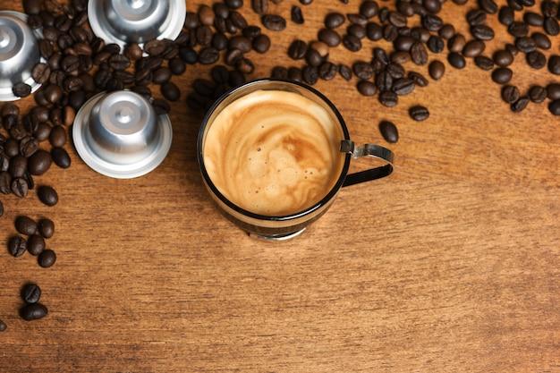 Tazza di caffè con capsule e chicchi di caffè