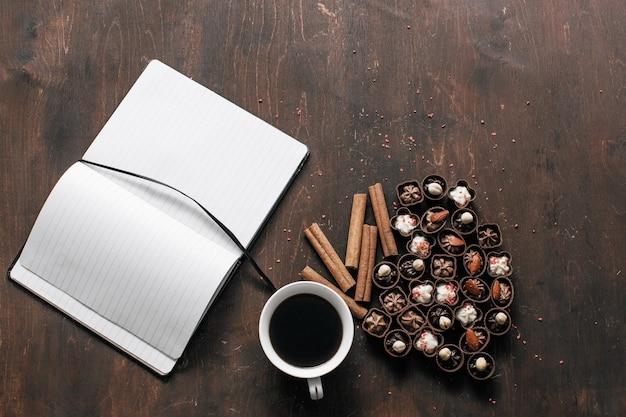 Tazza di caffè con caramelle al cioccolato e un blocco note