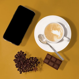 Tazza di caffè con cioccolato, fagioli a forma di cuore, telefono su un tavolo