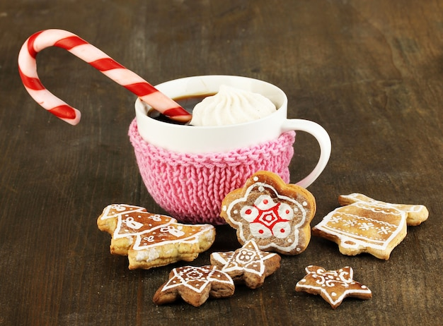Tazza di caffè con dolcezza natalizia sul primo piano della tavola di legno