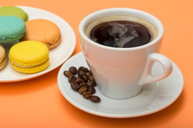 Tazza di caffè con chicchi di caffè e deliziose torte di macarons di colore diverso su piatto di porcellana bianca con sfondo color pesca. messa a fuoco selettiva sulla tazza