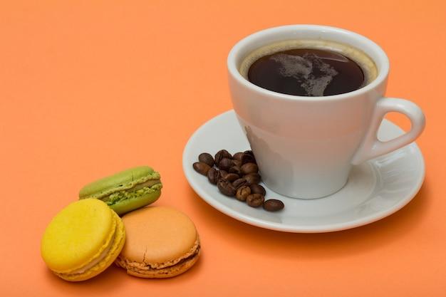 Tazza di caffè con chicchi di caffè e deliziose torte di macarons di colore diverso con sfondo color pesca