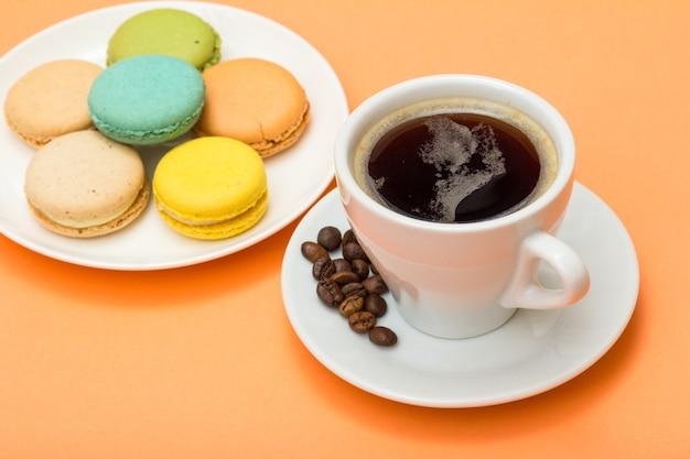 Tazza di caffè con chicchi di caffè sul piattino e deliziose torte di macarons di colore diverso su piatto di porcellana bianca con sfondo color pesca. messa a fuoco selettiva sulla tazza