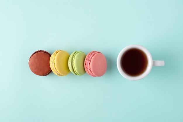 Una tazza di caffè con macarons colorati sulla superficie blu