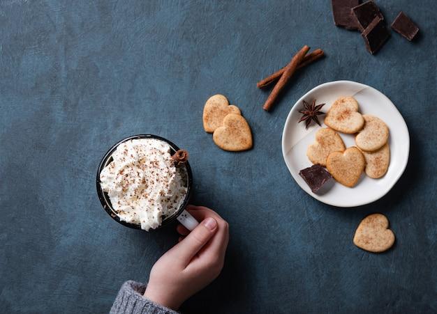 Una tazza di caffè con crema e scaglie di cioccolato in mano su un tavolo blu scuro con biscotti fatti in casa, cioccolato e cannella. vista dall'alto e copia spazio