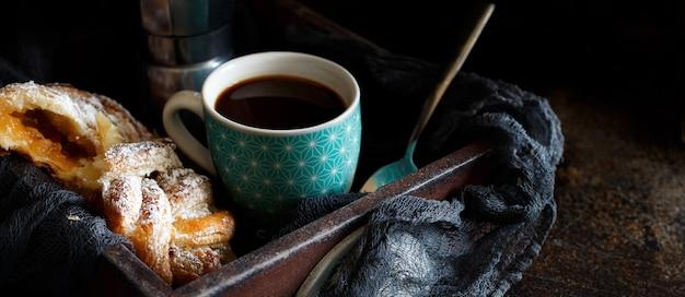 Tazza di caffè con croissant su uno sfondo scuro da vicino