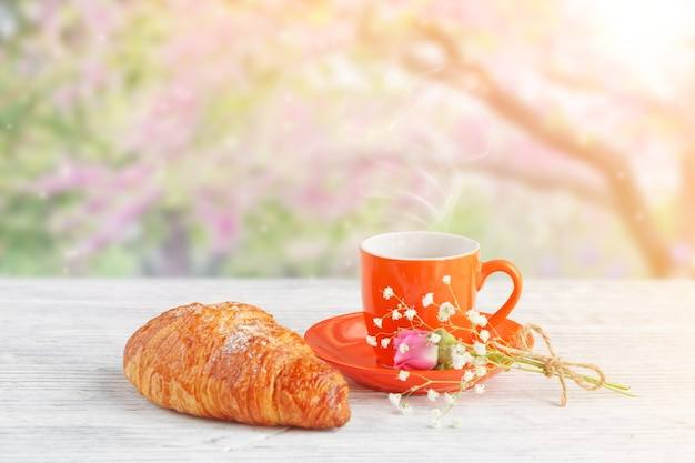 Tazza di caffè con croissant su un tavolo contro l'albero rosa in fiore